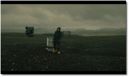 NF The Search struggling to pull a shopping cart with black balloons attached across a vast plain away from distant cage (30 May 2019)