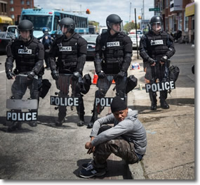 Baltimore teen chillin' on the curb in front of a phalanx of police in riot gear